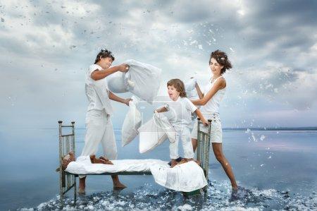 Photo pour Joyeux jeune famille combattre une bataille par des oreillers sur un lit dans la mer - image libre de droit