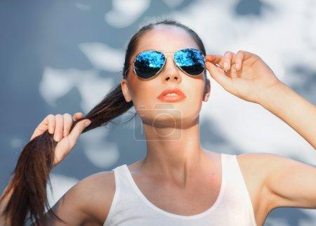 Attractive girl in mirrored blue sunglasses