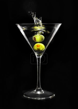 Photo for Splashing green olive in martini glass on black background - Royalty Free Image