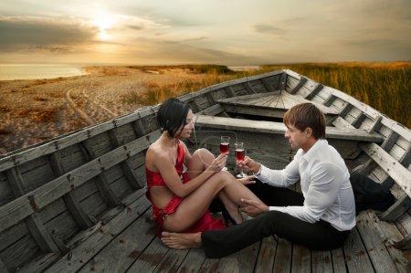 Photo pour Couple romantique amoureux de verres de vin dans un vieux bateau au bord de la mer au coucher du soleil - image libre de droit
