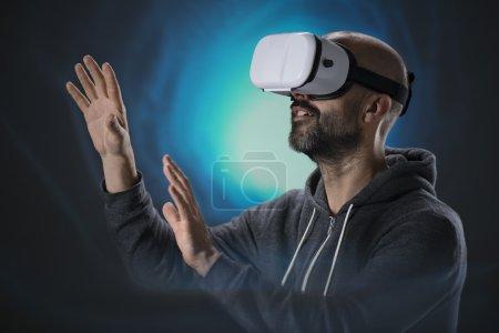 Photo pour Homme aux lunettes de réalité virtuelle devant un fond abstrait - image libre de droit