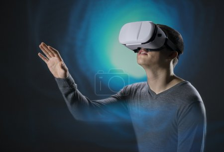 Photo for Young man wearing  virtual reality glasses in front of blue background animation wearing - Royalty Free Image