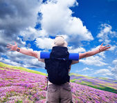 Hiker with black rucksack spreads hands expressing happiness