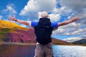 Hiker with black rucksack spreads hands expressing happiness at beautiful nature location