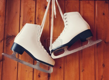 white ice skates for figure skating, hanging on a wooden backgro