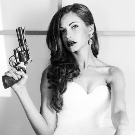 Photo pour Belle fille dans une robe de mariée avec un pistolet, tir de studio. Image en noir et blanc. - image libre de droit
