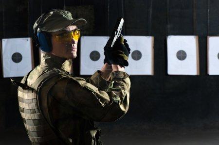 Photo for Man shooting with gun at a target in shooting range - Royalty Free Image