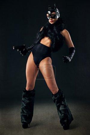 Photo pour Femme sexy en costume de catwoman noir avec pistolet - image libre de droit