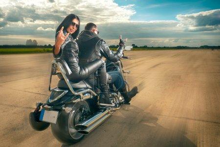 Photo pour Biker Homme et femme portant des vestes en cuir noir et des lunettes de soleil élégantes à moto - image libre de droit
