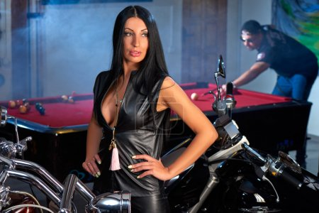 Young beautiful woman posing near motorbikes, man ...