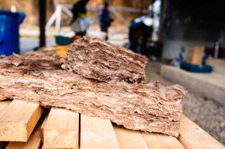 Foto de Piezas de lana de aislamiento de vidrio colocadas en vigas de madera colocadas en el sitio de construcción - Imagen libre de derechos