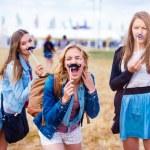 Teenage girls at summer music festival having fun ...