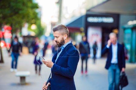 Photo pour Gestionnaire Hipster tenant un téléphone intelligent textos et écouter de la musique à l'extérieur dans la rue - image libre de droit