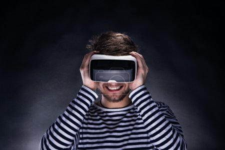 Photo for Hipster man in striped black and white sweatshirt wearing virtual reality goggles. Studio shot on black background - Royalty Free Image
