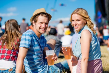 Young couple with beer at summer music festival