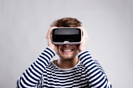 Photo for Hipster man in striped black and white sweatshirt wearing virtual reality goggles. Studio shot on gray background - Royalty Free Image