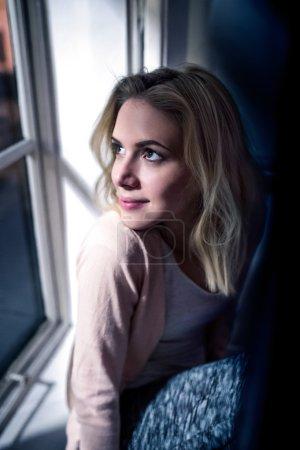 Foto de Hermosa mujer rubia sentada en el alféizar de la ventana por la noche, mirando por la ventana - Imagen libre de derechos