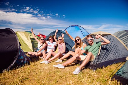 Teenagers sitting in front of tents
