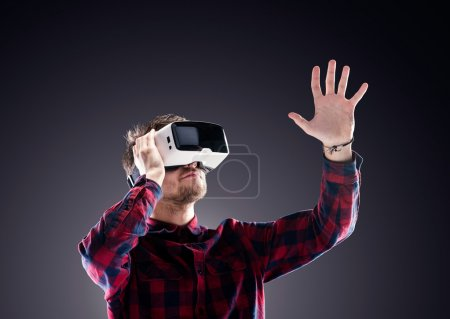 Photo for Hipster man in checked shirt wearing virtual reality goggles, reaching out. Studio shot on black background - Royalty Free Image