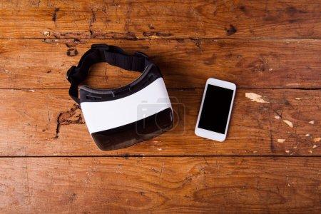 Photo pour Gros plan des lunettes de réalité virtuelle et du téléphone intelligent posés sur une table. Pose plate. Studio tourné sur fond en bois . - image libre de droit