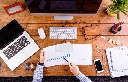 Foto de Persona de negocios en el despacho trabajando con el gráfico de la tabla. Teléfono inteligente, notebook, notepad y lentes y varios suministros de oficina en el lugar de trabajo. Endecha plana. - Imagen libre de derechos