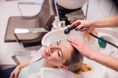 Photo pour Coiffeur professionnel méconnaissable lavant les cheveux à sa belle cliente. Jeune femme dans un salon de coiffure - image libre de droit
