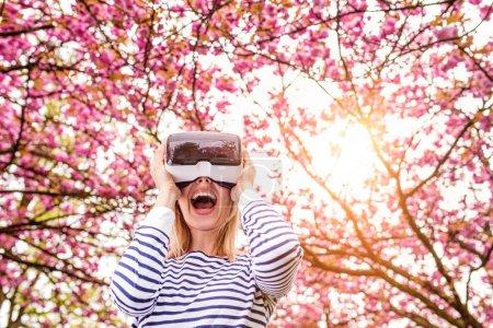 Photo pour Femme blonde portant des lunettes de réalité virtuelle à l'extérieur au printemps nature - image libre de droit