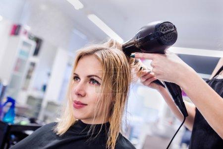 Photo pour Mains de coiffeur professionnel méconnaissable séchant les cheveux de sa cliente, nouvelle coupe de cheveux, cliente blonde . - image libre de droit