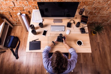 Photo for Photographer at the desk, wearing smart watch, working with camera.  Computer, smart phone and various object lens around the workplace. - Royalty Free Image