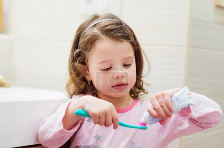 Little girl with toothpaste and toothbrush