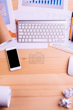 Photo for Desk with gadgets and office supplies. Computer keyboard, smart phone and stationery around the workplace. Flat lay. Studio shot on wooden background. Copy space. - Royalty Free Image