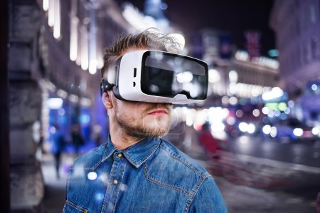 Photo for Hipster man in denim shirt wearing virtual reality goggles. City at night. London, England. - Royalty Free Image