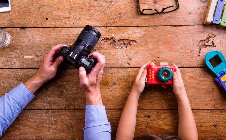 Photo pour Mains du père et du fils méconnaissables retenant des appareils-photo, vieux bureau de bureau. Studio tourné sur le fond en bois. Laïc plat. - image libre de droit