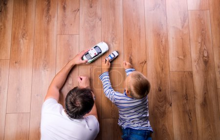 Photo for Unrecognizable father with his son playing with cars. Studio shot on wooden background. - Royalty Free Image