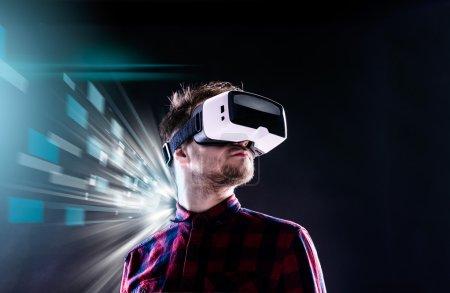 Photo pour Homme hipster en chemise à carreaux portant des lunettes de réalité virtuelle, les tenant. Studio tourné sur fond noir - image libre de droit