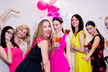 Photo for Cheerful bride and happy bridesmaids celebrating hen party with drinks. Women enjoying a bachelorette party dancing. - Royalty Free Image