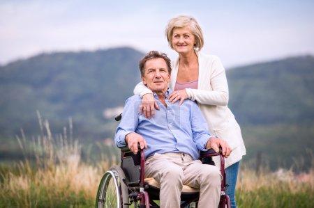 Senior woman pushing man in wheelchair, green autumn nature