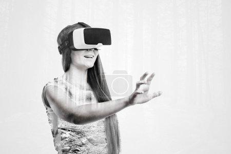 Photo pour Double exposition. Belle femme portant des lunettes de réalité virtuelle étirant le bras. Forêt, arbres . - image libre de droit