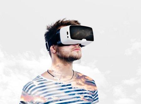 Photo pour Double exposition. Homme hipster en sweat-shirt rayé noir et blanc portant des lunettes de réalité virtuelle. Ciel et nuages . - image libre de droit