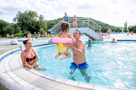 Photo for Young mother and father lifting up their daughter in inflatable ring in swimming pool in aqua park. Summer heat and water. - Royalty Free Image