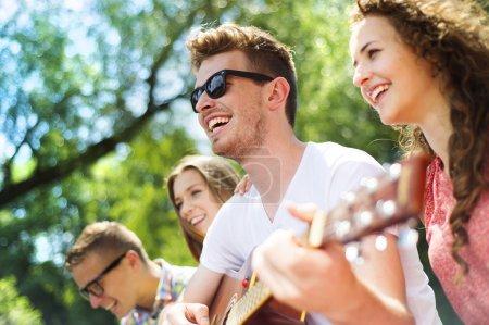 Photo pour Groupe d'amis heureux avec guitare s'amuser en plein air - image libre de droit