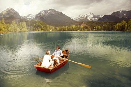 Senior couple paddling on boat