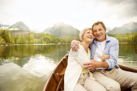 Photo for Senior couple hugging on boat with mountains in background - Royalty Free Image