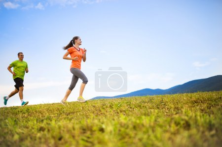 Photo for Cross-country trail running people at sunset. Runner couple exercising outside as part of healthy lifestyle. - Royalty Free Image