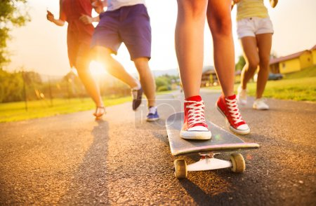 Photo for Closeup of legs and sneakers of young people on skateboard - Royalty Free Image