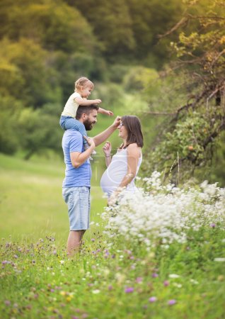 Photo for Happy pregnant family having fun in summer nature - Royalty Free Image