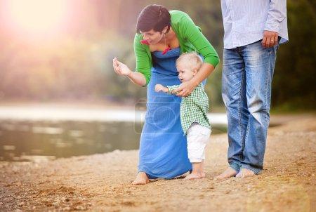 Photo pour Joyeux jeune famille passer l'été ensemble au bord du lac sur la plage de sable - image libre de droit
