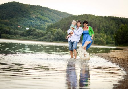 Foto de Happy young family spending summer time together by the lake on the sandy beach - Imagen libre de derechos