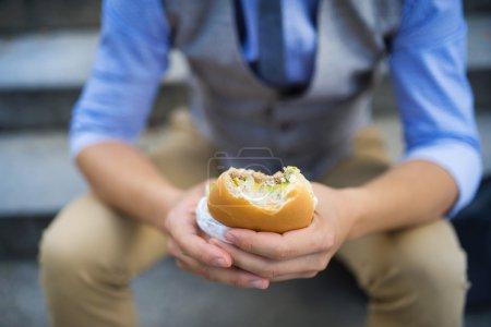 Hands are holding hamburger.