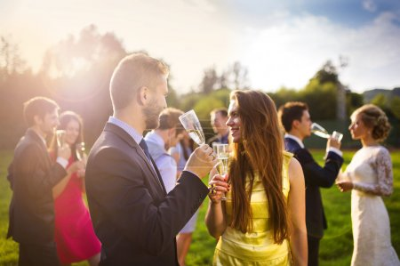 Photo pour Wedding guests clinking glasses at the wedding reception outside - image libre de droit